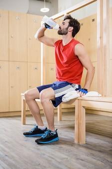 Handsome man drinking water in locker room