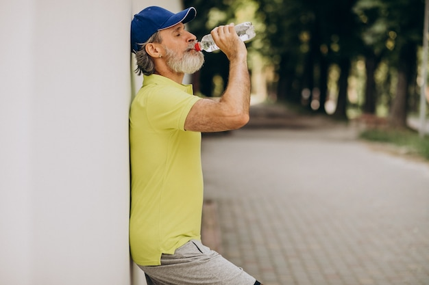 Handsome man drinking water in park after jogging