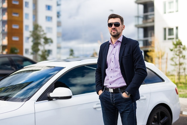 Handsome man driver in sunglasses posing near his car