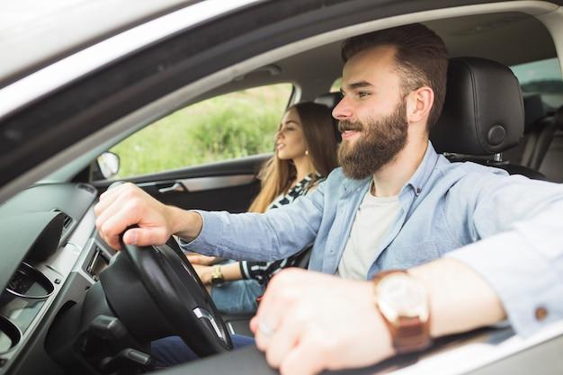 車で彼のガールフレンドと車を運転するハンサムな男