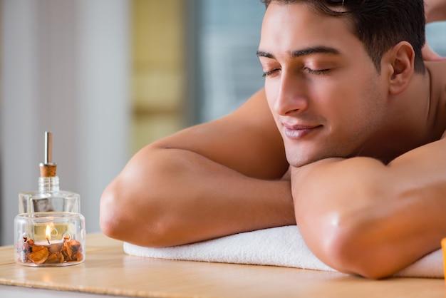 Красивый мужчина во время сеанса массажа в спа