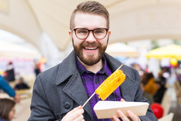 Красивый мужчина ест вкусные кукурузные початки на улице.