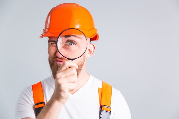 회색 벽에 보호 헬멧을 구축하는 잘 생긴 남자 엔지니어, 돋보기와 장난스럽고 긍정적 인