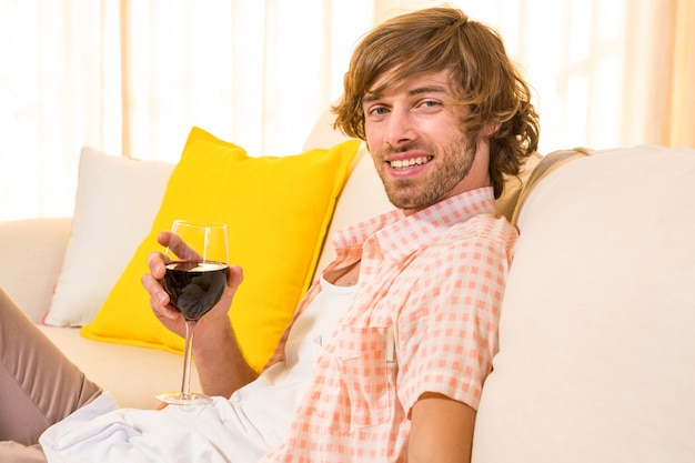 Handsome man enjoying a glass of wine on the couch in the living room