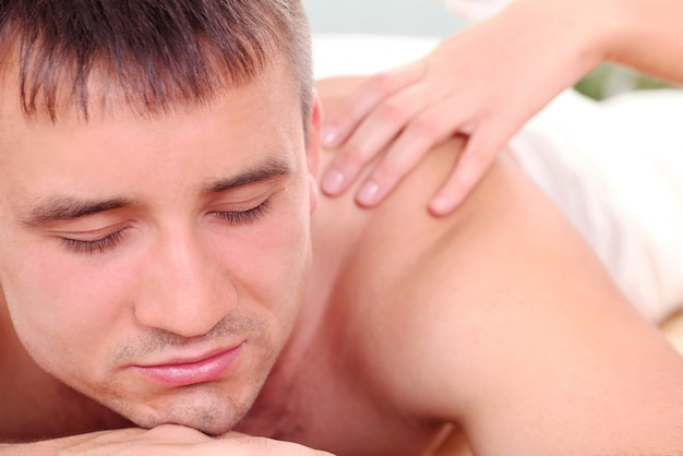 Handsome man enjoying procedure of massage