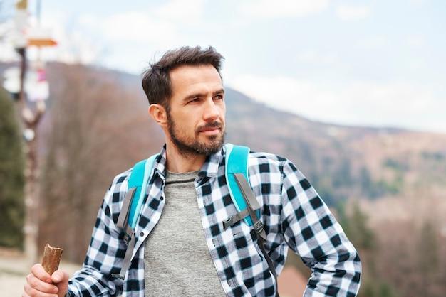 ハイキング旅行中に景色を楽しむハンサムな男