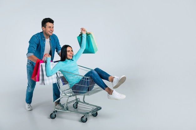 Handsome man in everyday clothes is pushing a shopping cart with a gorgeous girl with multicolored paper bags in her hands, inside.
