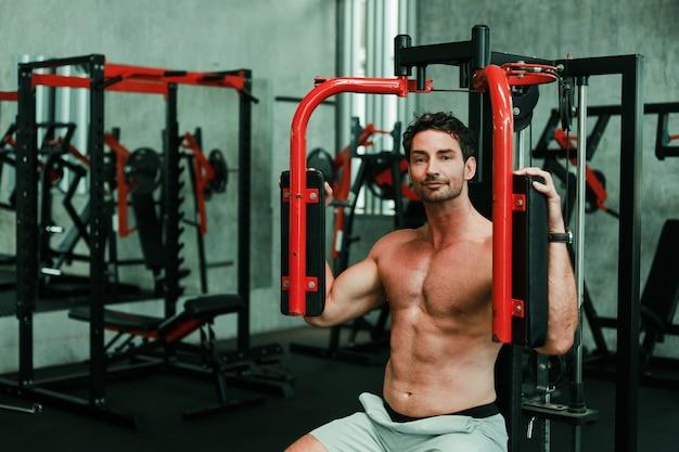 Красавец упражнения в бодибилдинге с мускулистым сильным телом