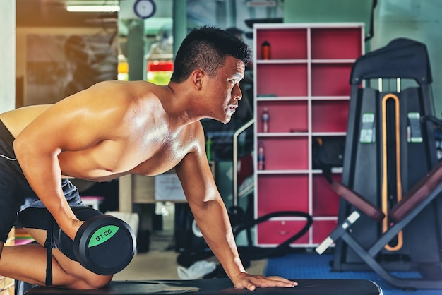 Handsome man exercising by lifting a dumbbell for health care in a public gym