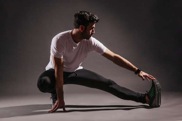 Handsome man exercising in dark studio