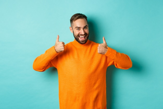 Handsome man expressing support, showing thumb up, encourage you, praise excellent work, approve and agree, standing over light blue background.