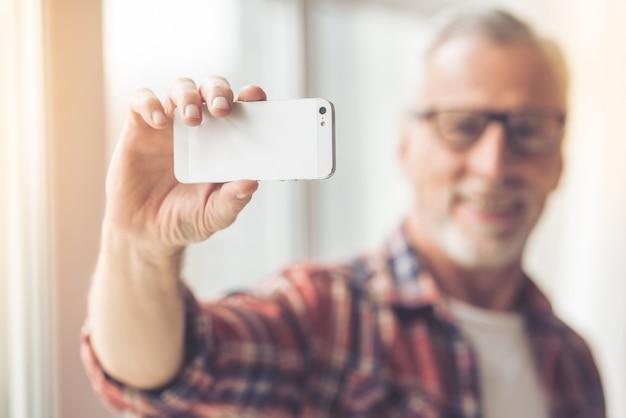 Handsome man in eyeglasses is doing selfie