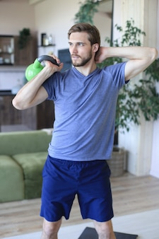 Handsome man focused on lifting a dumbbell during an exercise at home during quarantine.