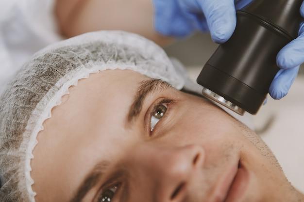 Handsome man getting facial skincare treatment