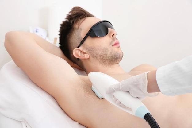 Красивый мужчина, получающий лазерную эпиляцию в салоне красоты