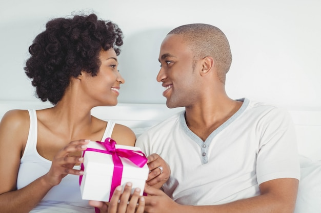Handsome man giving present to his girlfriend on the bed