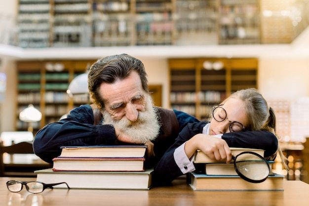 Handsome man grandfather and pretty little girl granddaughter fell asleep during reading books in old ancient library, sitting at the table over the vintage book shelves background