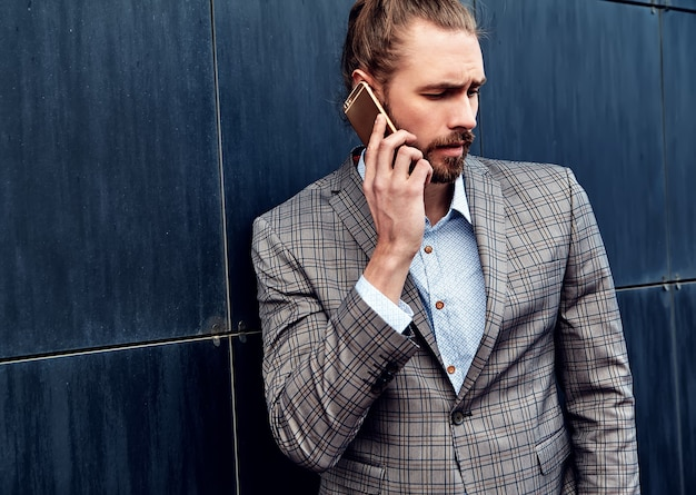 Handsome man in gray checkered suit speaking with smartphone
