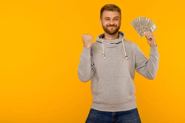 Handsome man in a gray hoodie enjoys winning the lottery money dollars on a yellow background - image