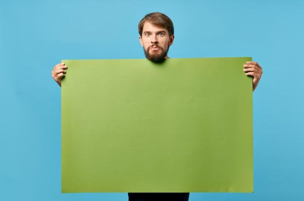 手でハンサムな男の緑のバナー空白シート青い背景