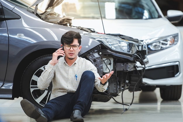 The handsome man had a stressful gesture after the damaged car was hit by an accident and used his phone to ask for help after the car hit the road - the car has accident insurance.