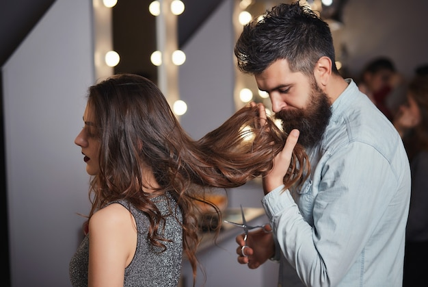 Handsome man hairdresser smelling hair of a beautiful girl in elegant evening dress.