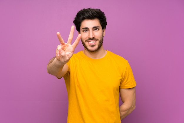 Handsome man happy and counting three with fingers