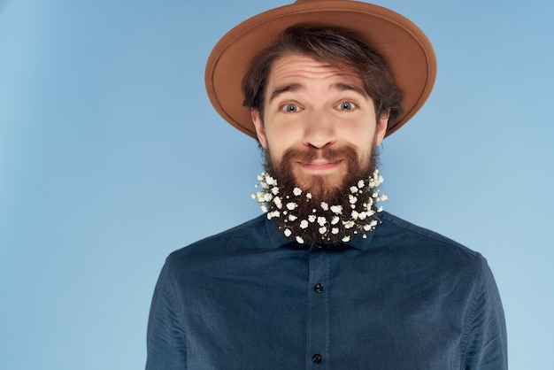 Handsome man in hat with blue shirt flowers in beard self confidence fashion