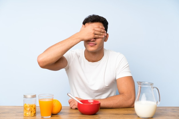 Handsome man in having breakfast covering eyes by hands