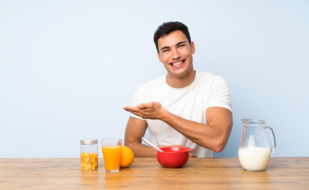 Handsome man in having breakfast extending hands to the side for inviting to come