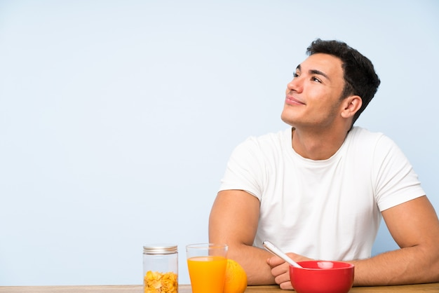 Handsome man in having breakfast laughing and looking up