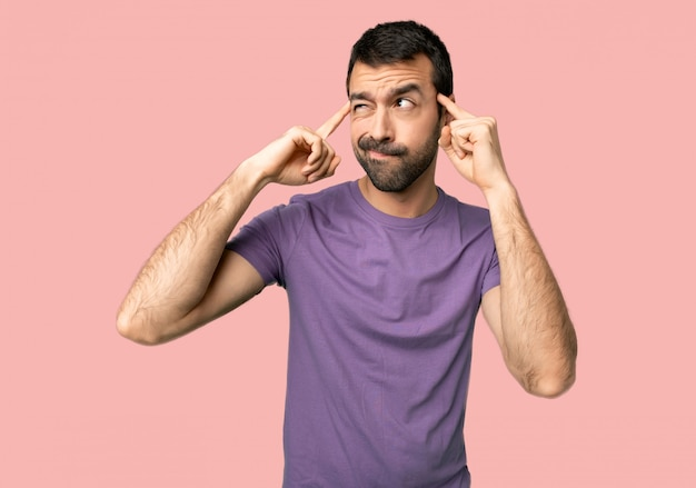 Handsome man having doubts and thinking on isolated pink background