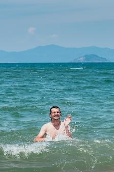 Красивый мужчина веселится в море, плещет воду вокруг милой улыбки, концепция летнего отдыха