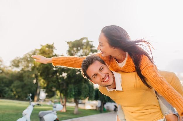 Красивый мужчина развлекается на свидании с радостной женщиной с каштановыми волосами, размахивающими руками