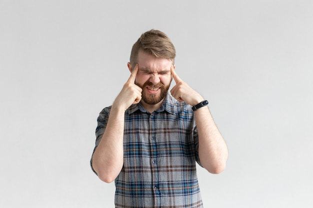 Handsome man having a headache on white wall.