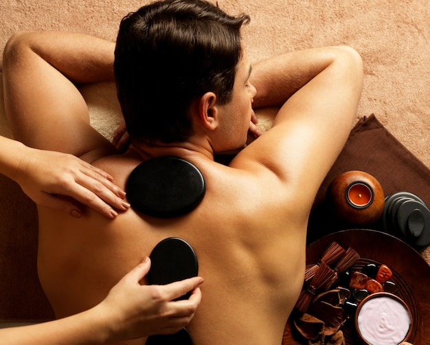 Handsome man having stone massage in spa salon. healthy lifestyle.