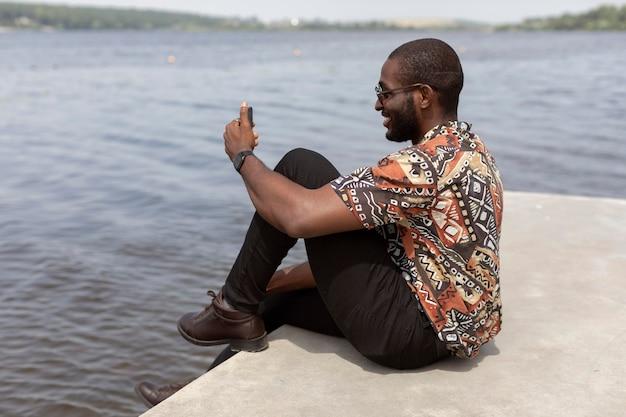 Bell'uomo che fa una videochiamata con uno smartphone moderno all'aperto