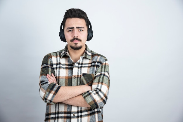 Bell'uomo in cuffia ascoltando musica sul muro bianco.