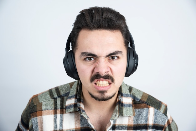 Handsome man in headphones looking angry over white wall.