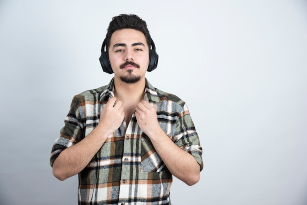 Handsome man in headphones looking to camera over white wall.