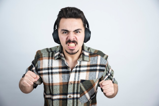 Handsome man in headphones screaming on white wall.