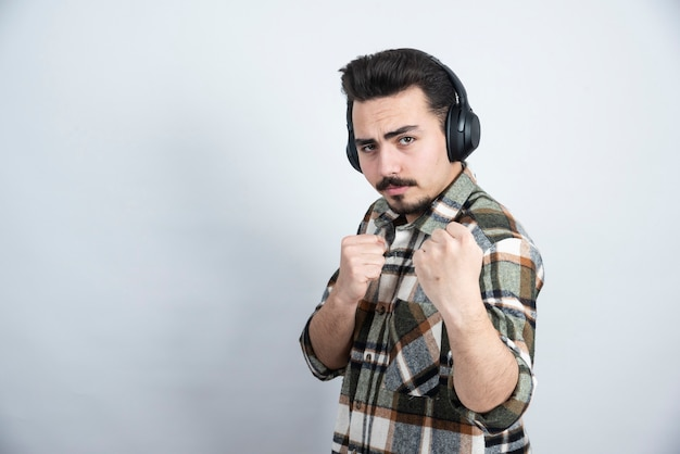Handsome man in headphones standing and posing to camera.