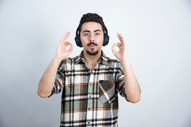 Handsome man in headphones standing on white wall.