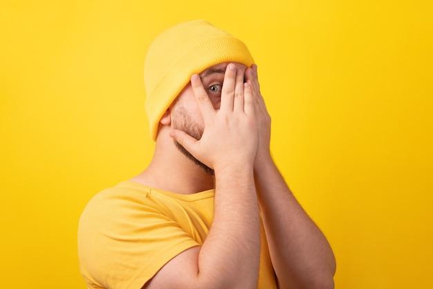 잘생긴 남자는 손으로 얼굴을 숨기고, 손바닥을 통해 보고, 노란색 배경 위에 수줍음을 느낀다