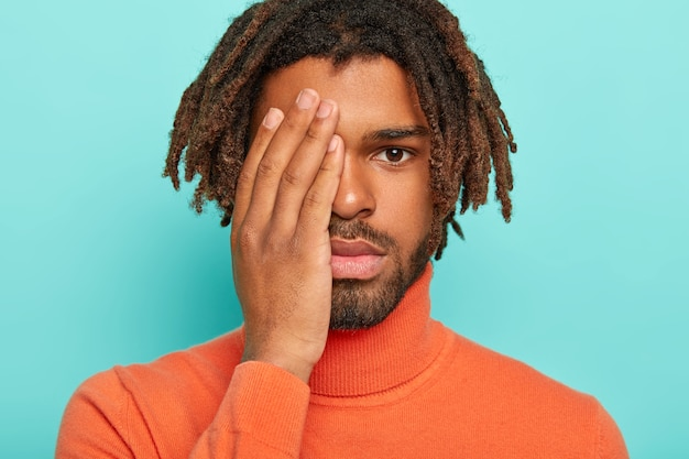 Handsome man hides half of face with palm, looks seriously at camera, has dark dreads, wears orange poloneck sweater, being tired after long work