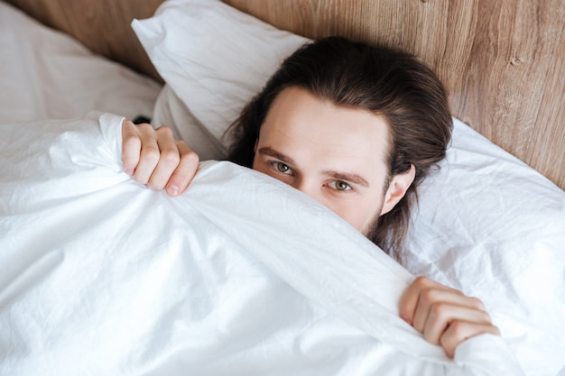 Handsome man hiding his face under white coverlet in bed