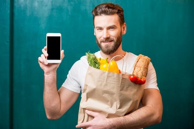 녹색 배경에 휴대 전화와 함께 건강 식품으로 가득 찬 종이 가방을 들고 잘 생긴 남자