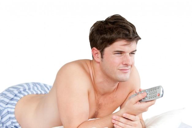 그의 침대에 누워 원격 들고 잘 생긴 남자