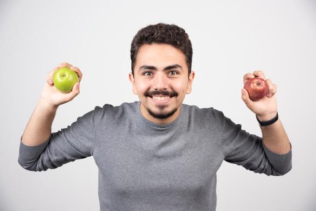 Uomo bello che tiene le mele su grigio.