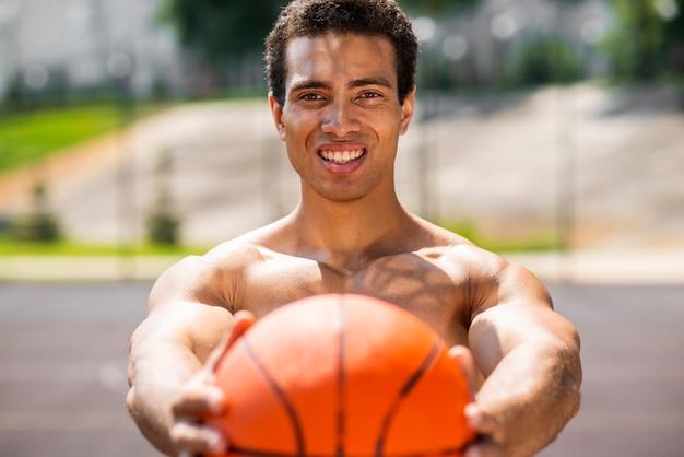 Handsome man holding a ball  medium shot